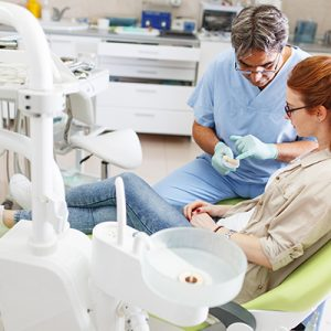 older-male-dentist-speaking-to-female-patient-in-dental-office