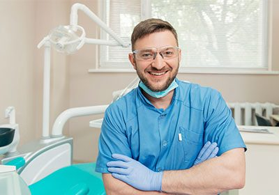male-dentist-smiling-with-arms-crossed